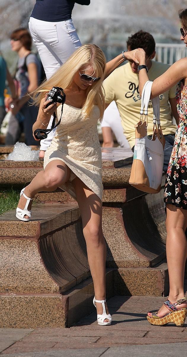 Блондинка в колготках и мини-платье засветила белые трусики