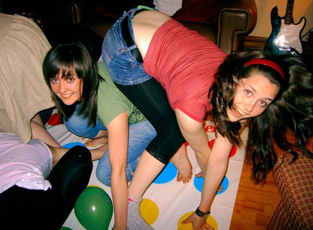 Сексуальные девушки в черных леггинсах играют в твистер
