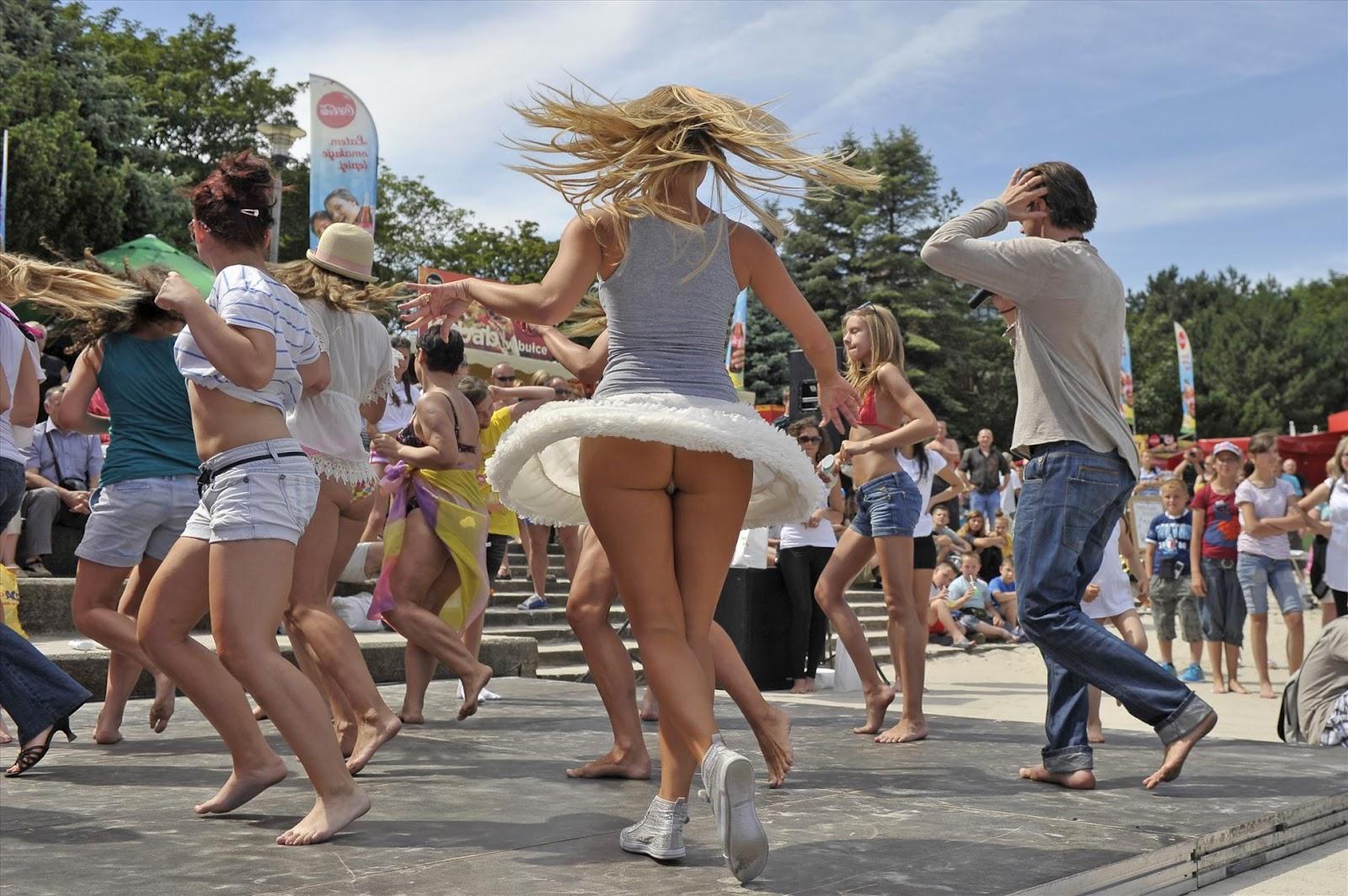 Сексуальная блондинка засветила под юбкой попку в белых стрингах