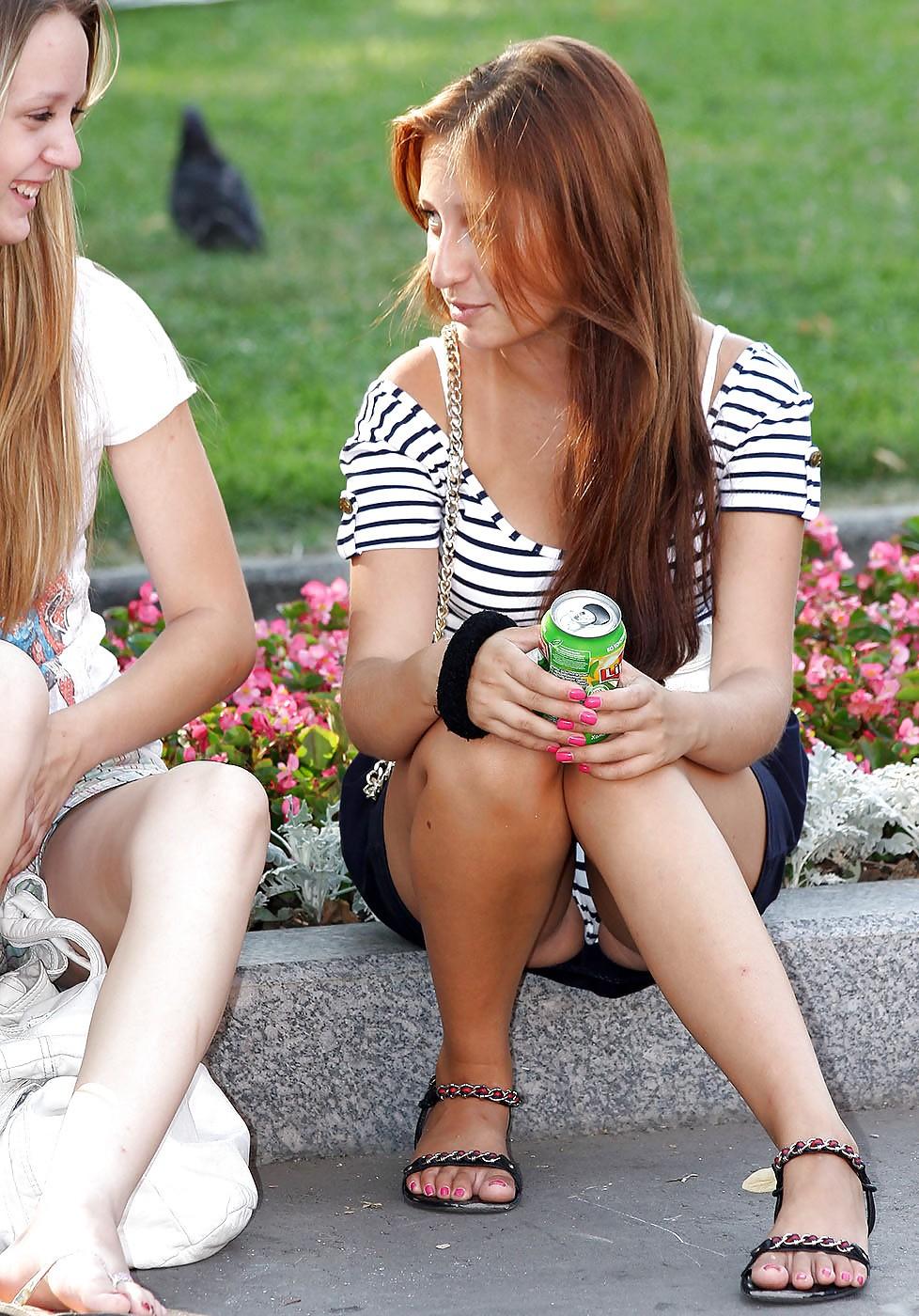 Рыжая девушка в мини-юбке засветила трусики в полоску