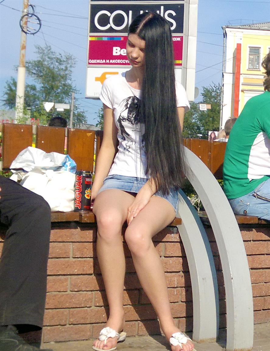 Длинноволосая брюнетка светит трусиками под джинсовой мини-юбкой