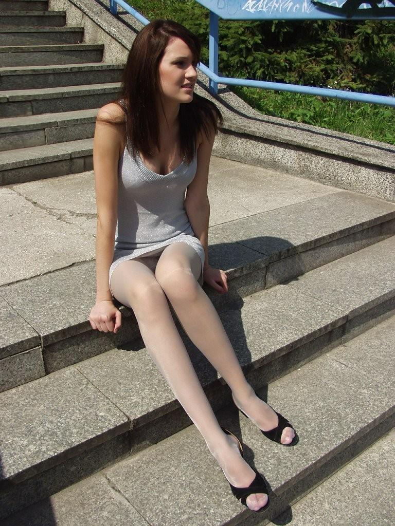 Брюнетка в сером мини-платье засветила белые колготки