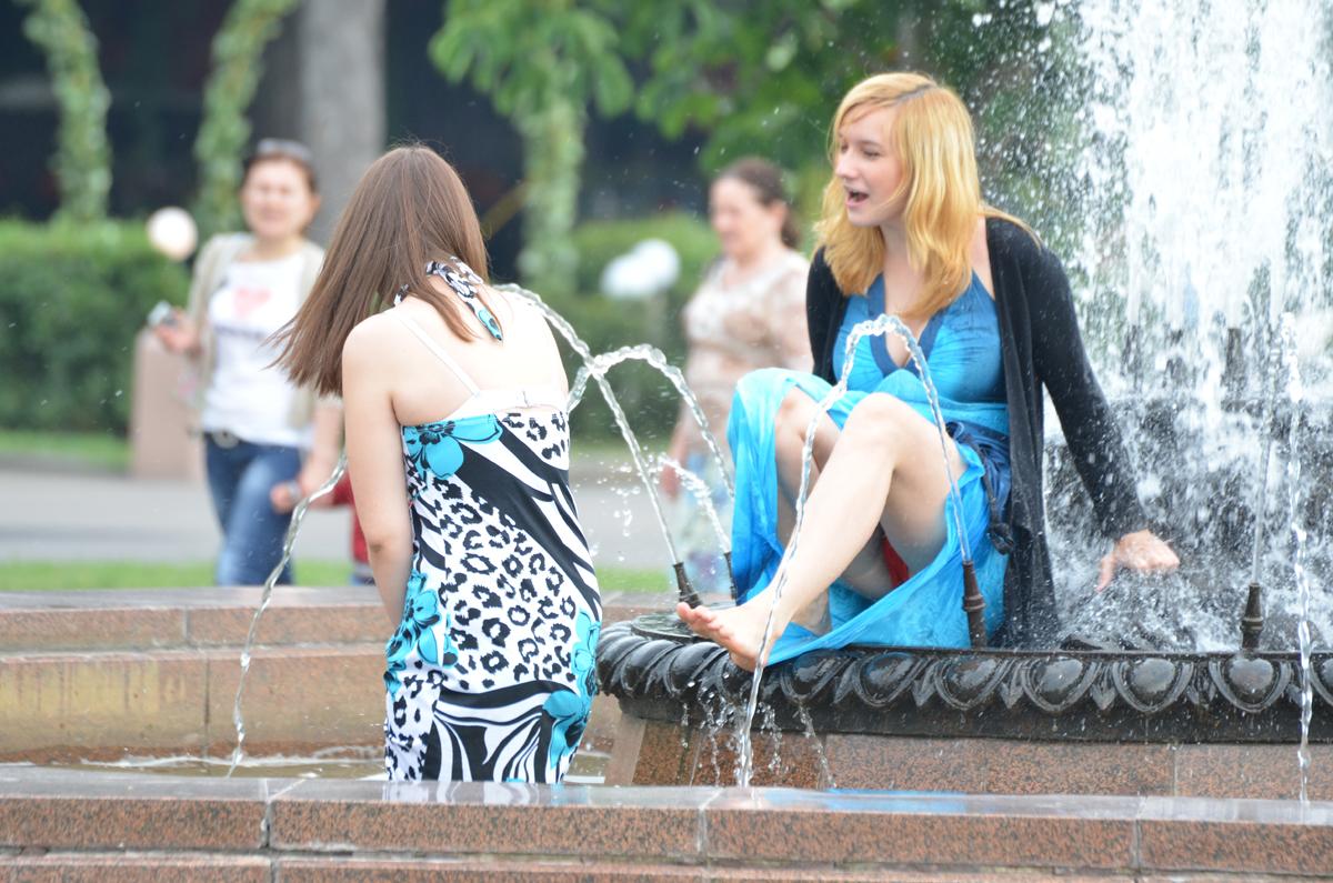 Девушка в синем платье засветила у фонтана красные трусики