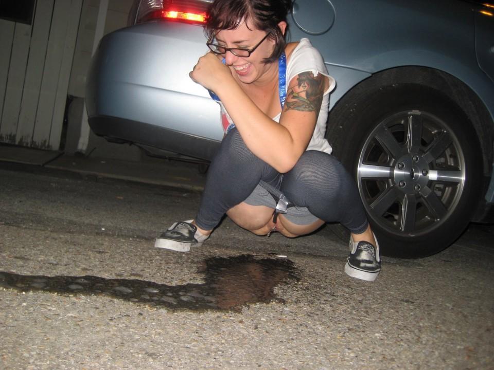 Девушка в серых леггинсах писает возле машины