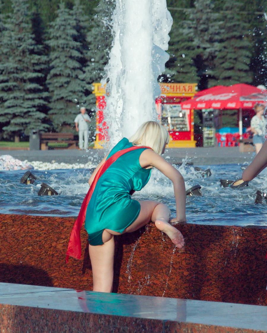 Блондинка в зеленом мини-платье засветила свою попку в стрингах