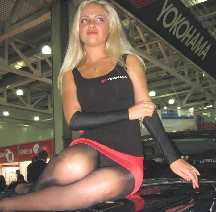 Блондинка засветила на автовыставке черные колготки под розовой юбочкой