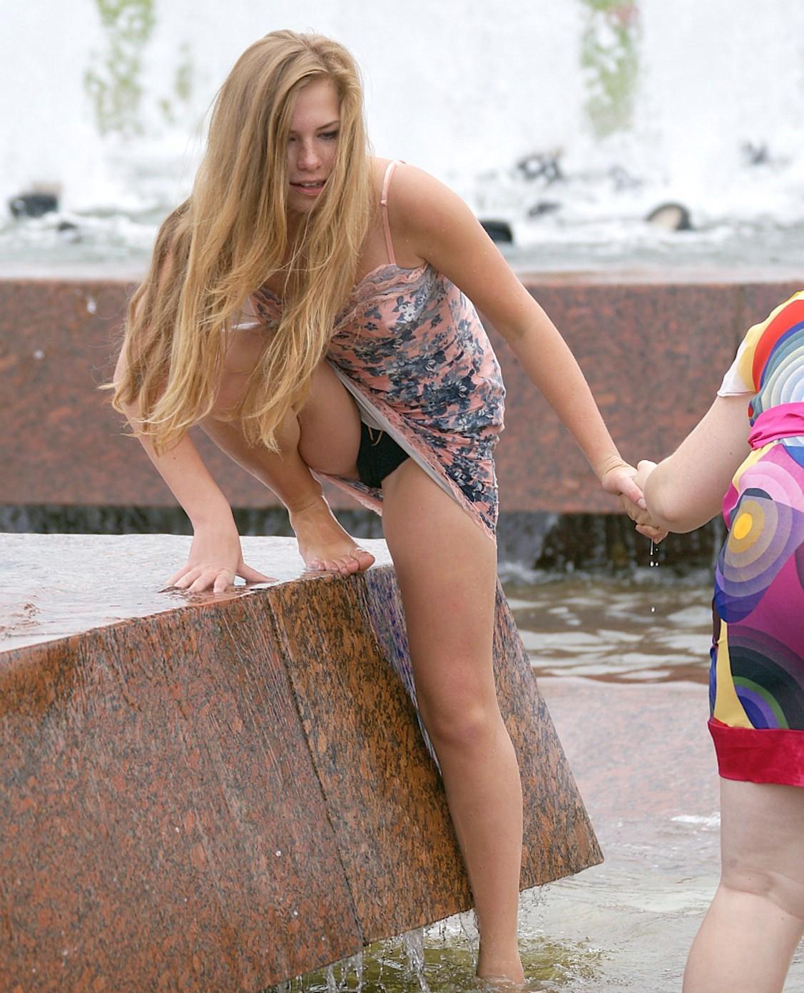 Блондинка купаясь в фонтане засветила черные трусики