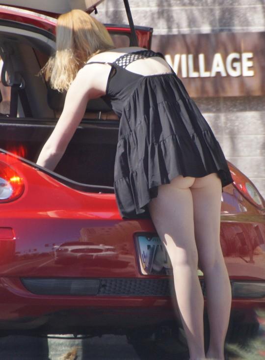 Блондинка в черном мини-платье засветила свою попку