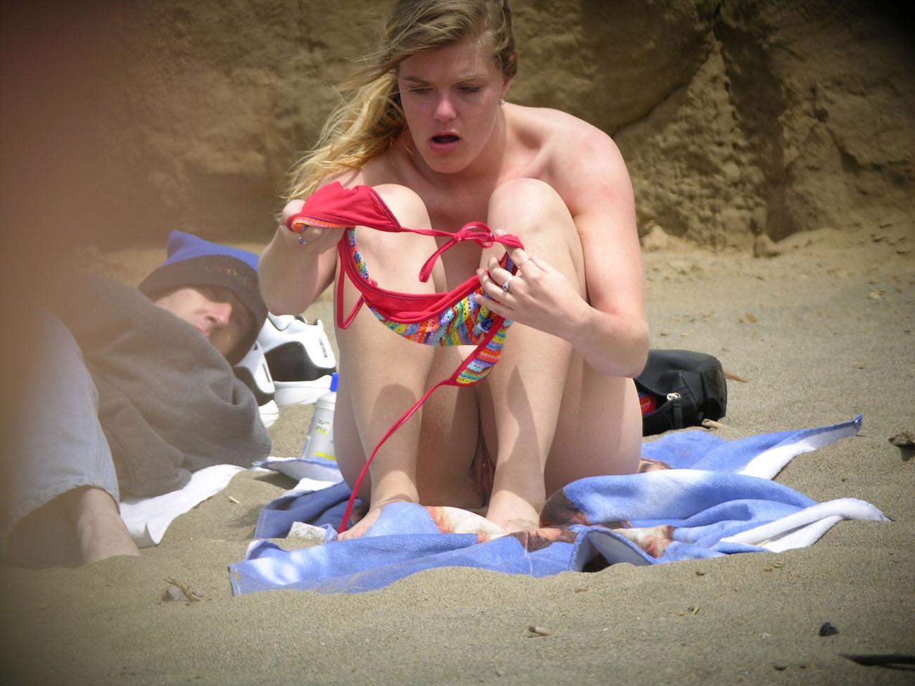 Сексуальная девушка переодевает трусики на пляже