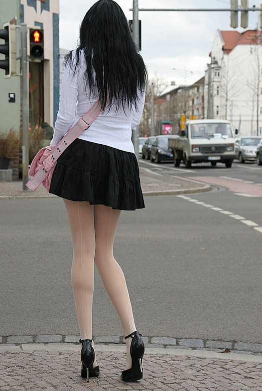 Сексуальная брюнетка в черной мини-юбке и белых колготках светит попкой