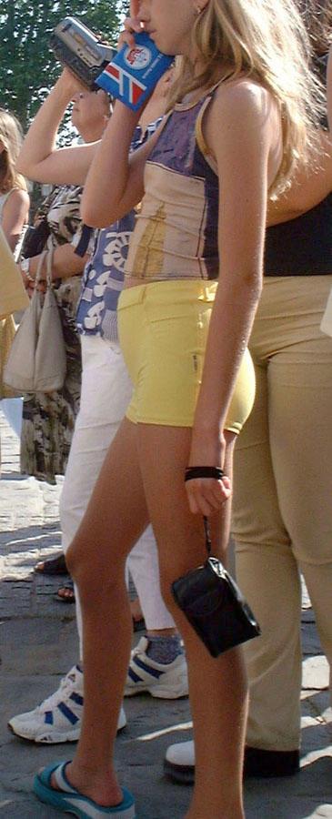Верблюжья лапка малолетки в желтых обтягивающих шортах