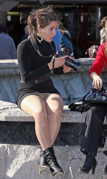 Девушка в черном платье светит трусиками под колготками