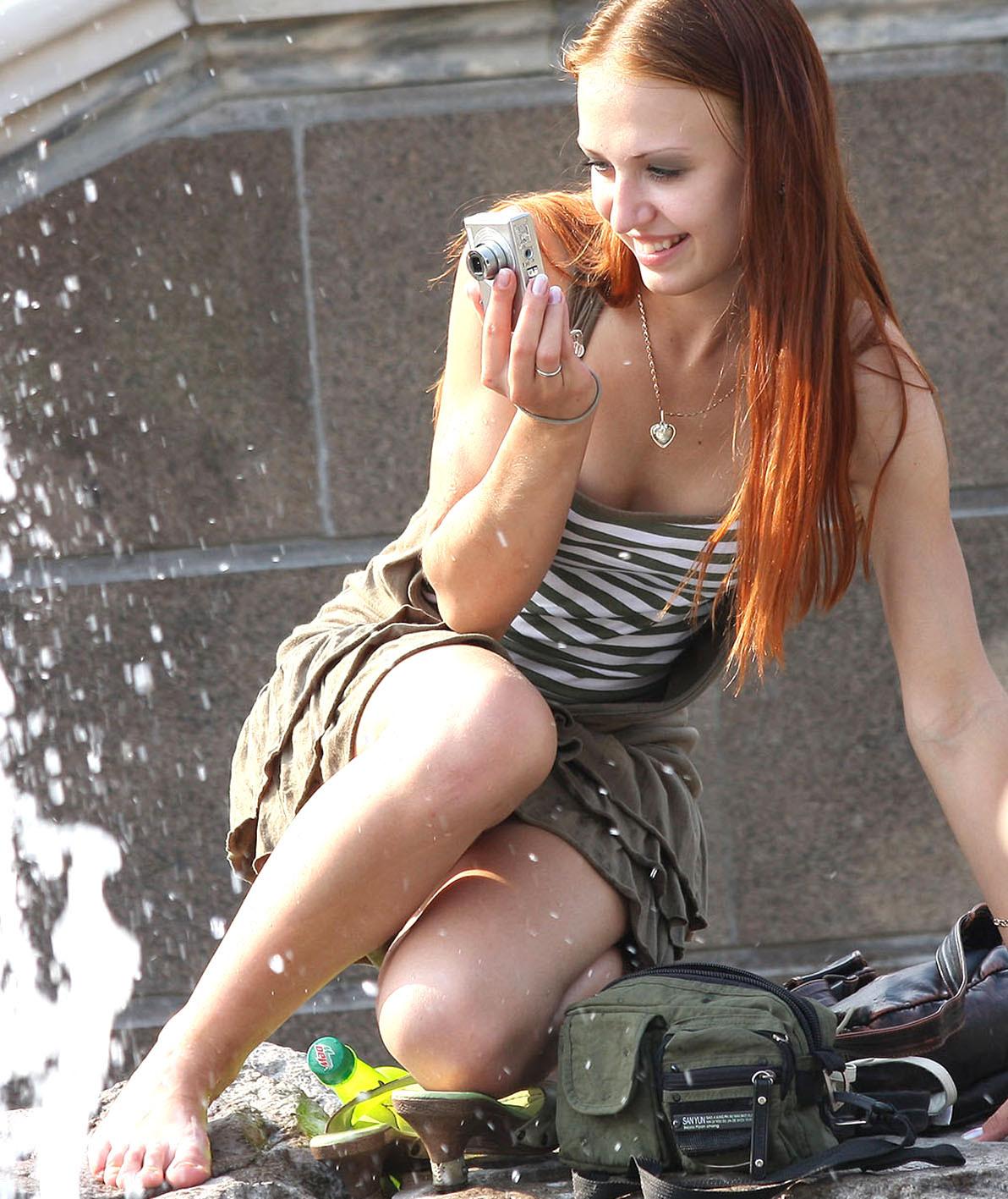 Рыжеволосая девушка засветила у фонтана белые трусики под короткой юбкой