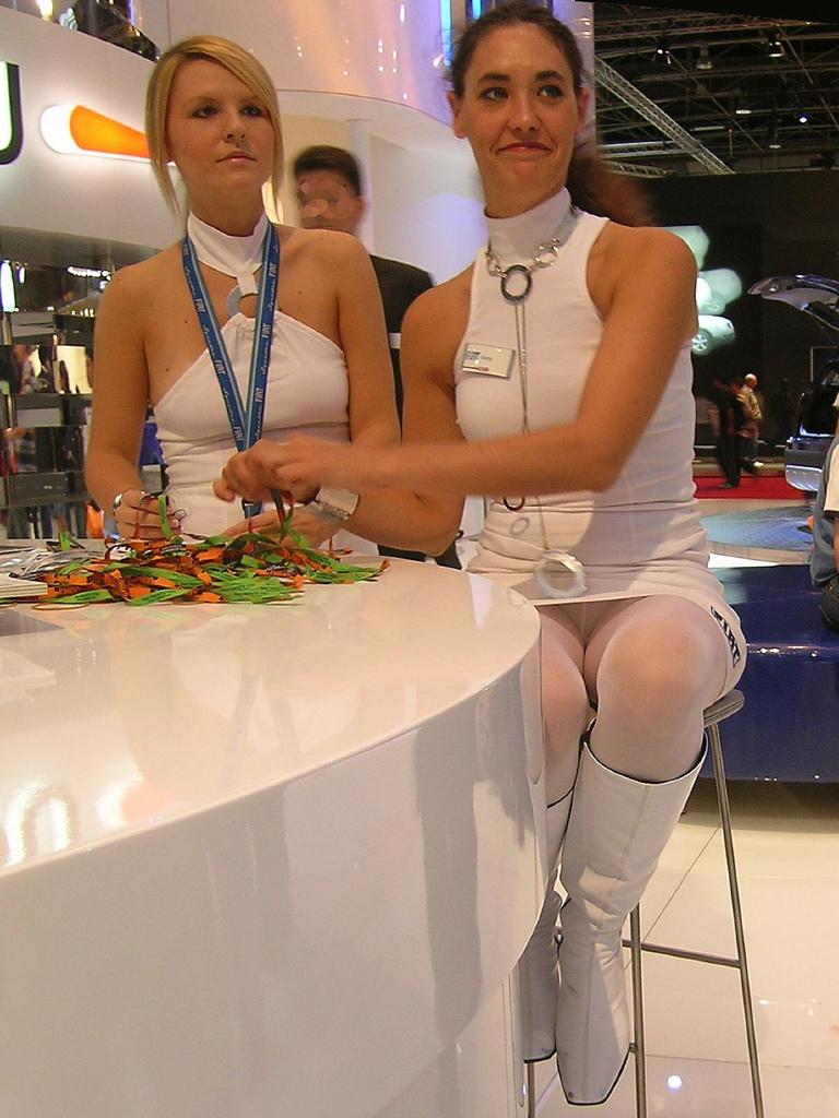 Девушка в белом мини-платье засветила колготки под юбкой