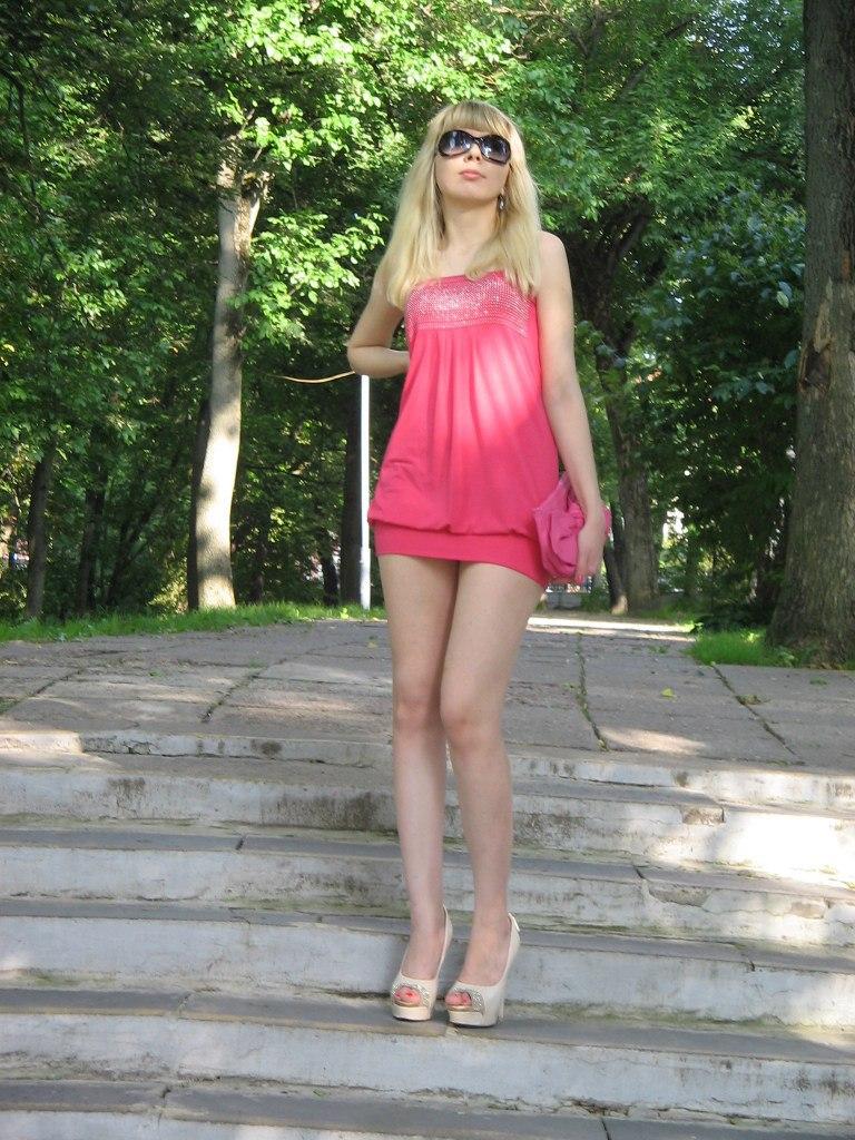 Блондинка в розовом мини-платье засветила трусики под юбкой
