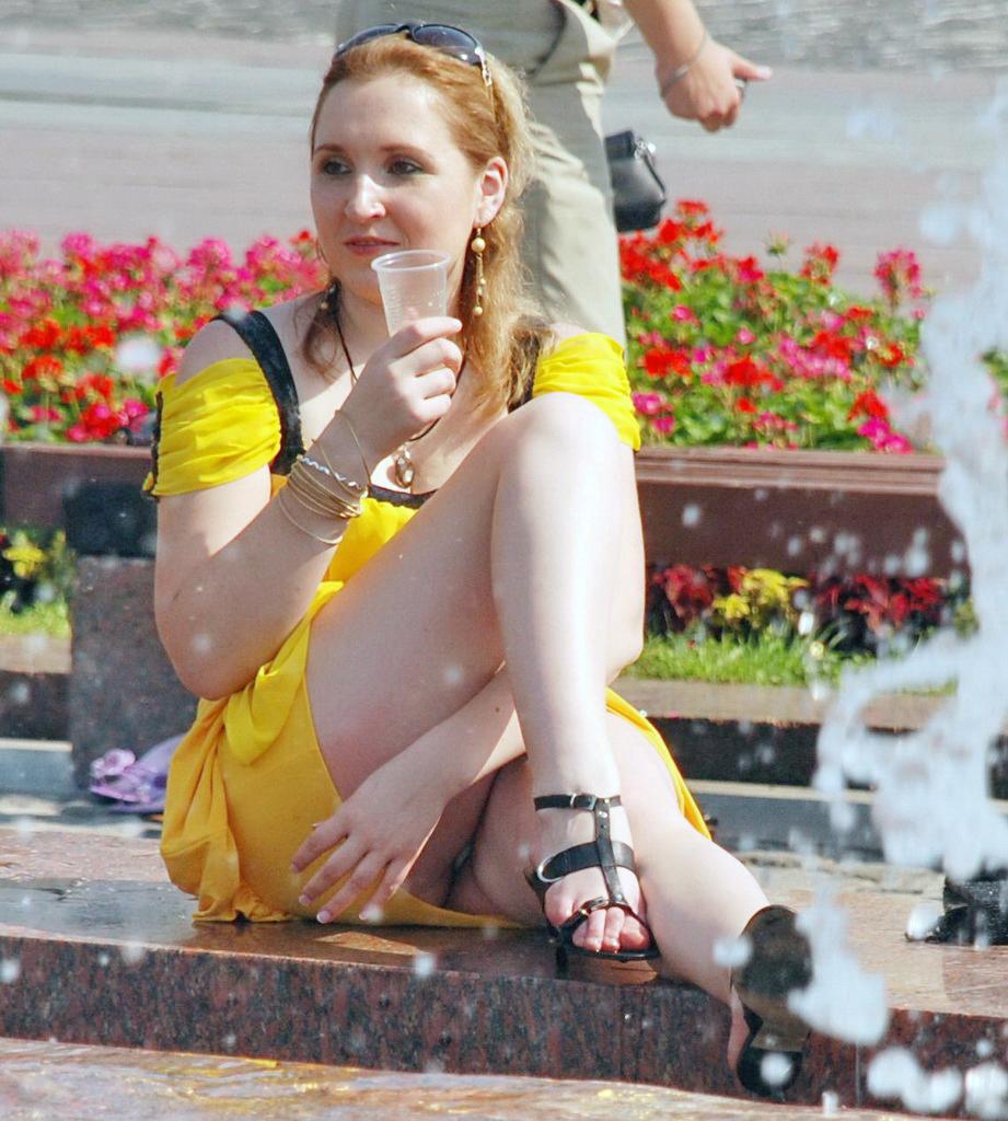 Девушка в желтом мини-платье засветила трусики у фонтана