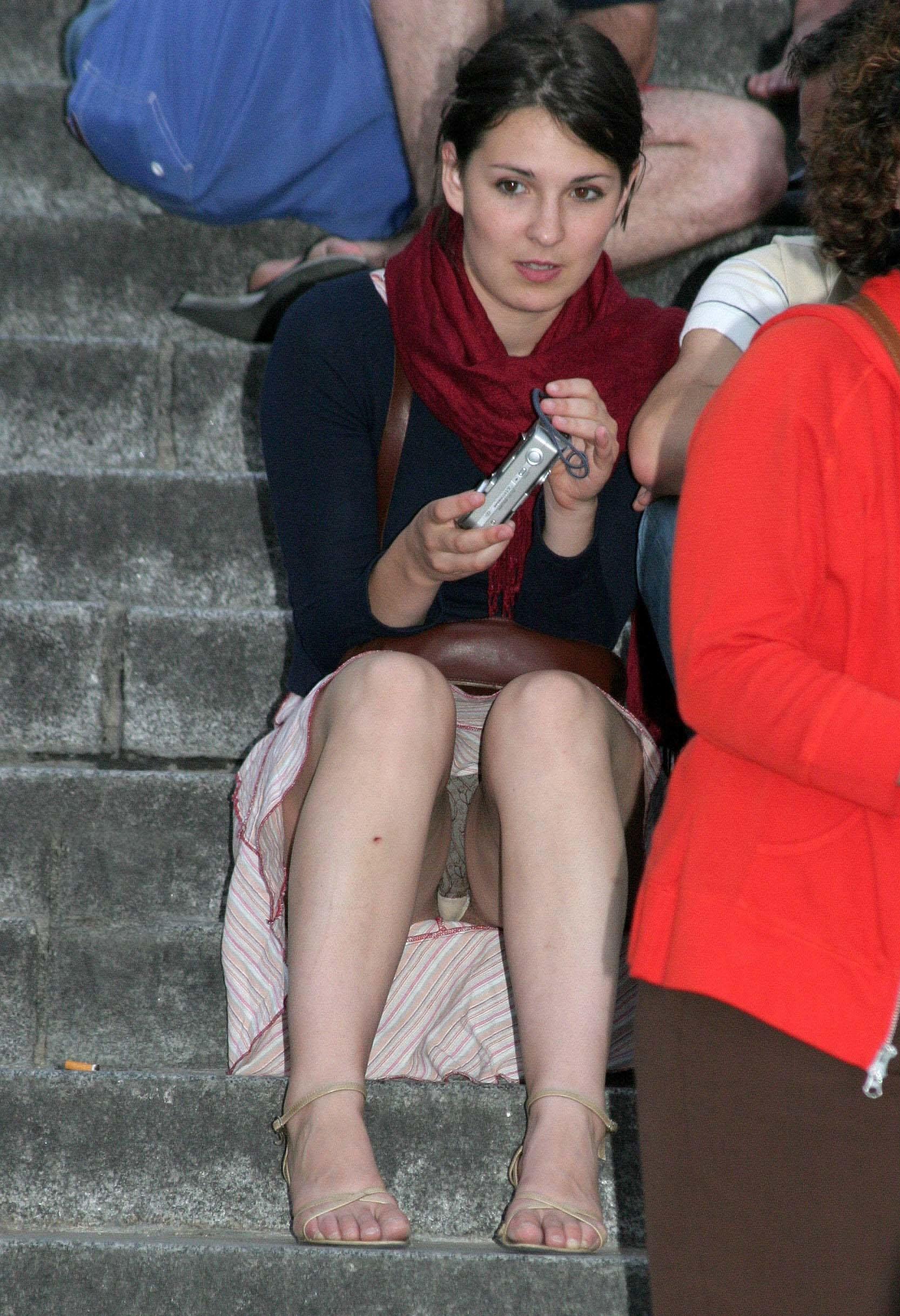 Брюнетка засветила трусики под юбкой сидя на лестнице